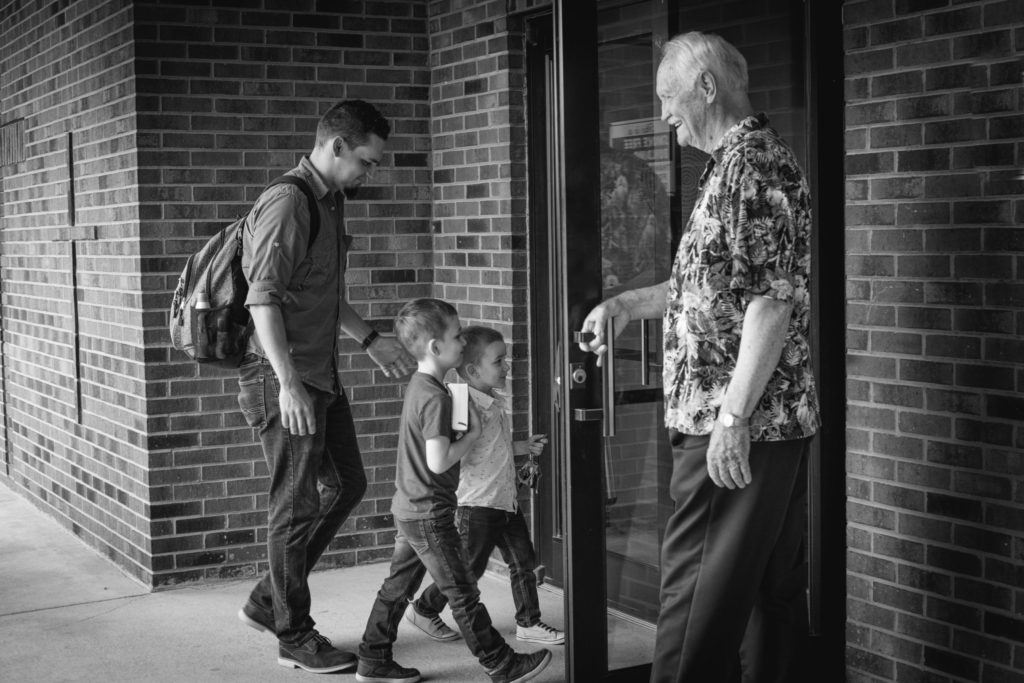 older man opening door for younger man and his kids to enter church, you're welcome here