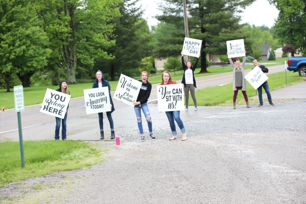 fun and friendly people holding welcome signs as people enter church parking lot