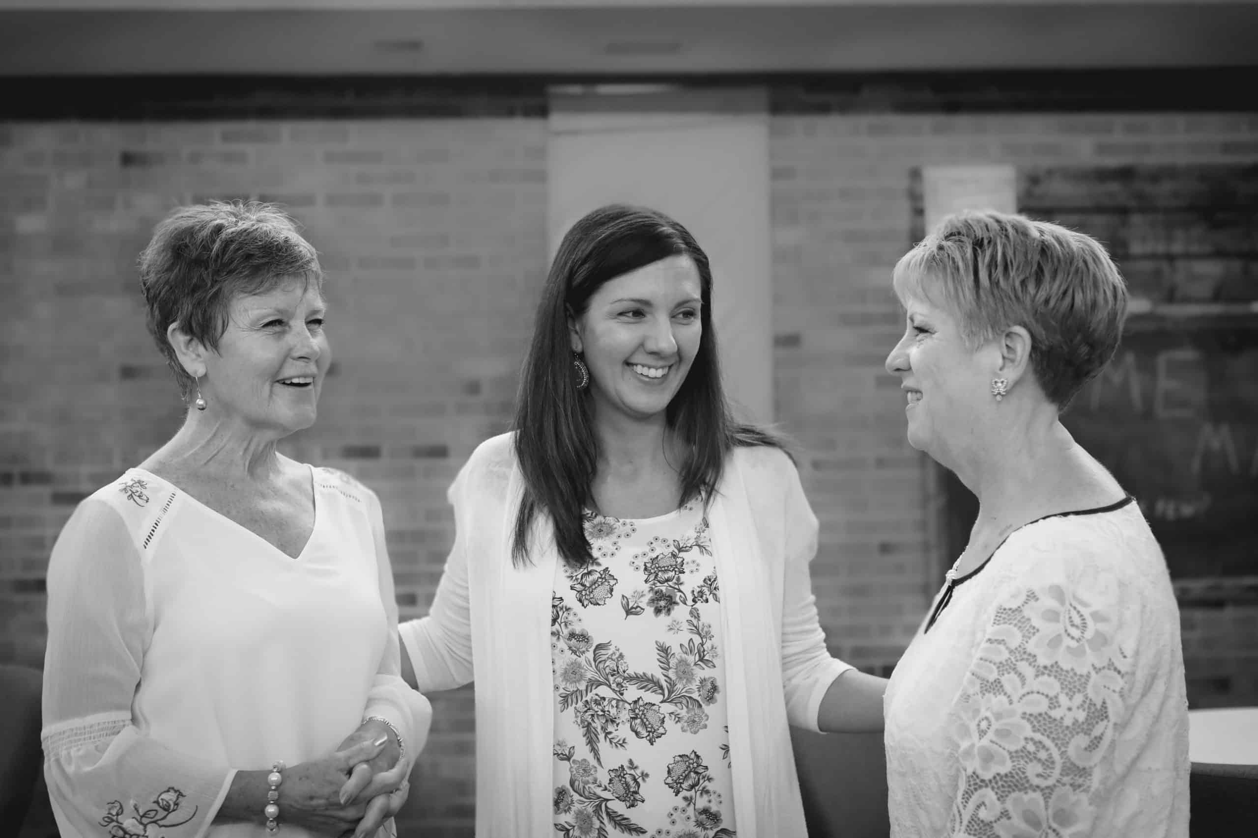 three women laughing together, one young and two older