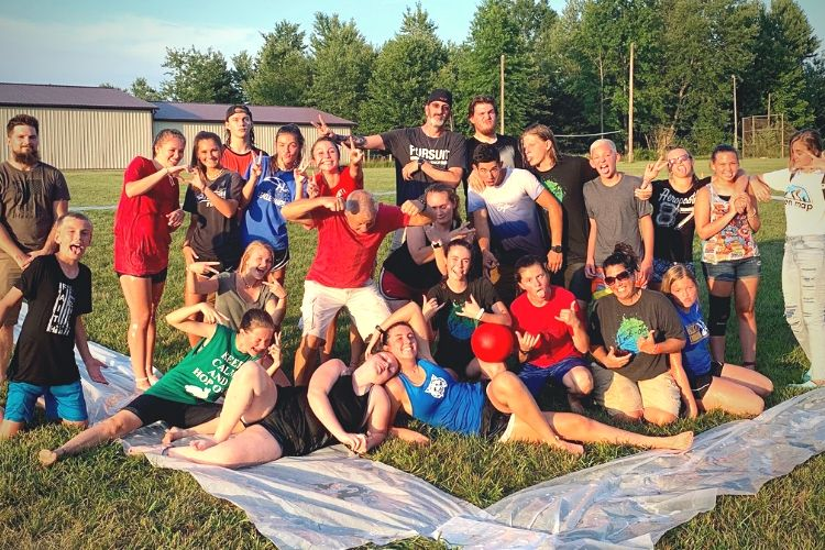 Youth group playing slip and slide kickball in a field