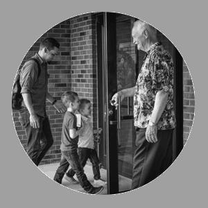 older gentleman opening door for family entering church