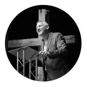 Preacher preaching from pulpir with wooden cross behind him