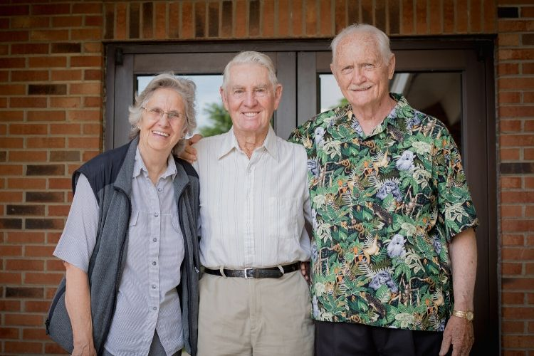 older gentlemen and older woman standing outside of church smiling