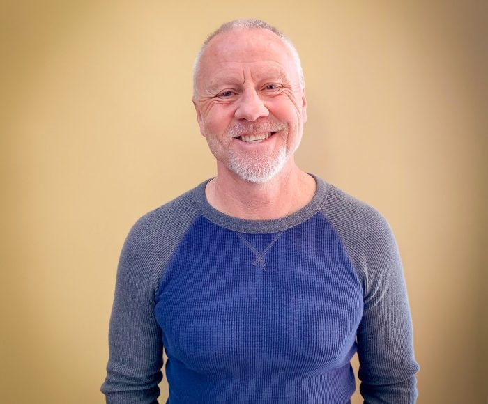older man smiling with blue shirt